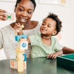 African American Toddler playing with mom and toys