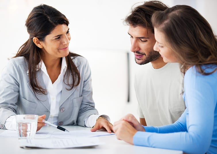 Caucasian female attorney reviews paperwork with young caucasian male and female couple
