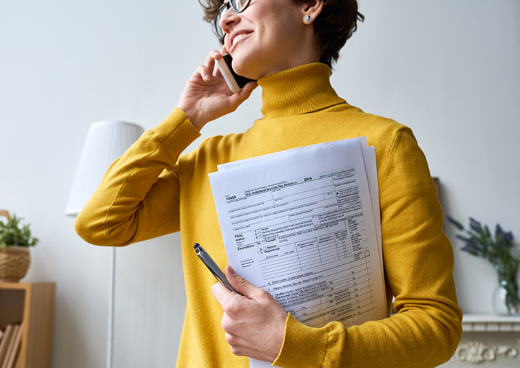 Cheerful woman in yellow sweater calling on phone and holding income tax return papers