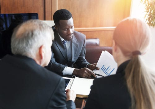 African American Male going over evaluation with a mature caucasian couple at a desk