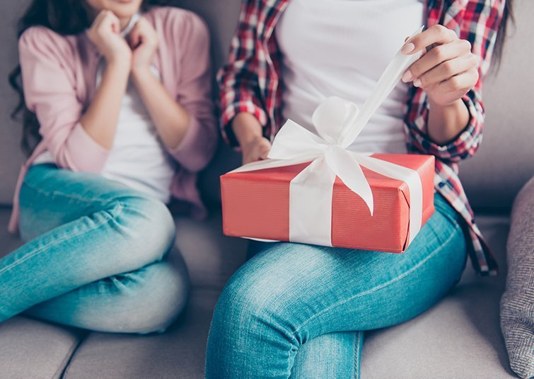 Cropped close up photo of woman's hands unpacking red gift box on her knees, she is touching white ribbon, her little daughter is waiting for mother's reaction