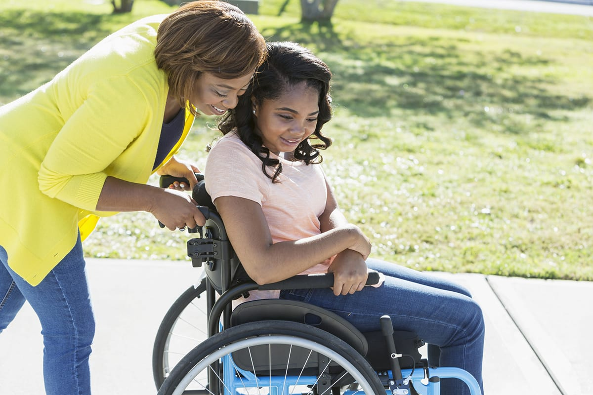 An African-American woman walking with her daughter who is a paraplegic in a wheelchair, outdoors. She is 15 years old, mixed race African-American and Hispanic.